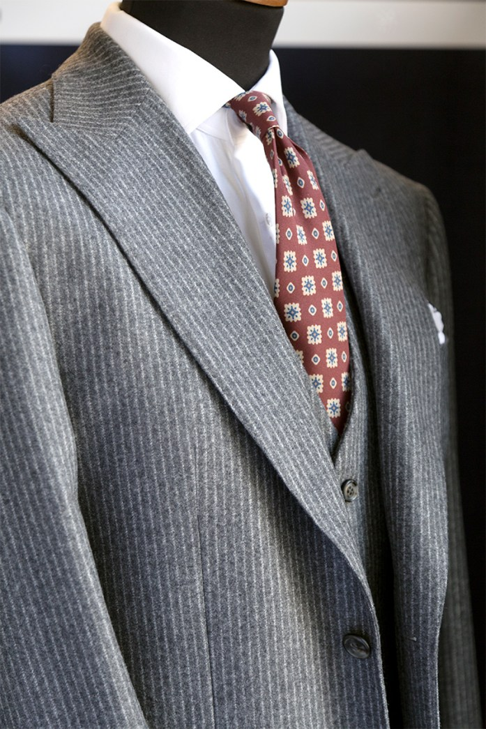 Light gray pinstripe three-piece suit with white shirt and burgundy tie with yellow and blue pattern