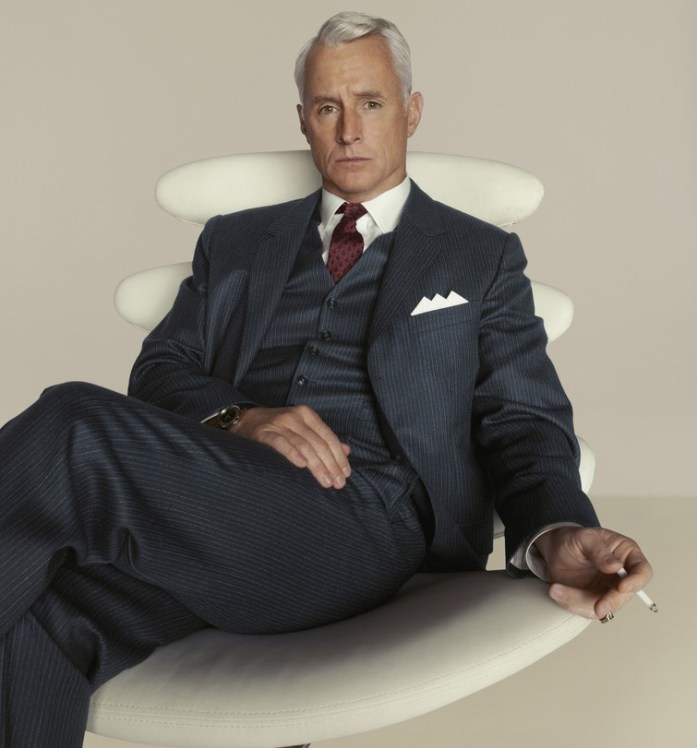Actor John Slattery plays the character in the Mad Men series Roger Sterling wearing a pinstripe dark gray three-piece suit, a three-corner up folded white pocket square, a burgundy tie and a white shirt, sits on a white armchair smoking a cigarette