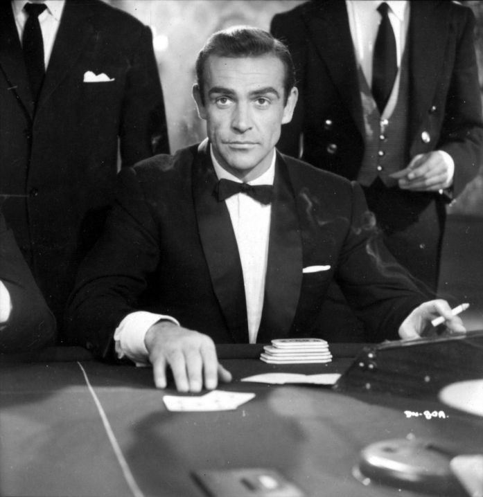 Actor Sean Connery plays James Bond 007 in a scene from the movie Casino Royale (1967) wearing a black tuxedo, a white flat-fold pocket square, while smoking a cigarette sitting at the game table