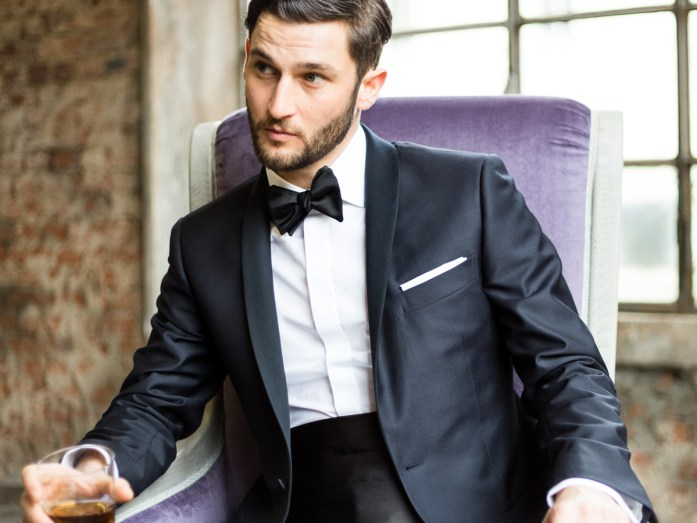 Man sitting on a purple armchair, wearing a black tuxedo by day with white shirt and black bow tie