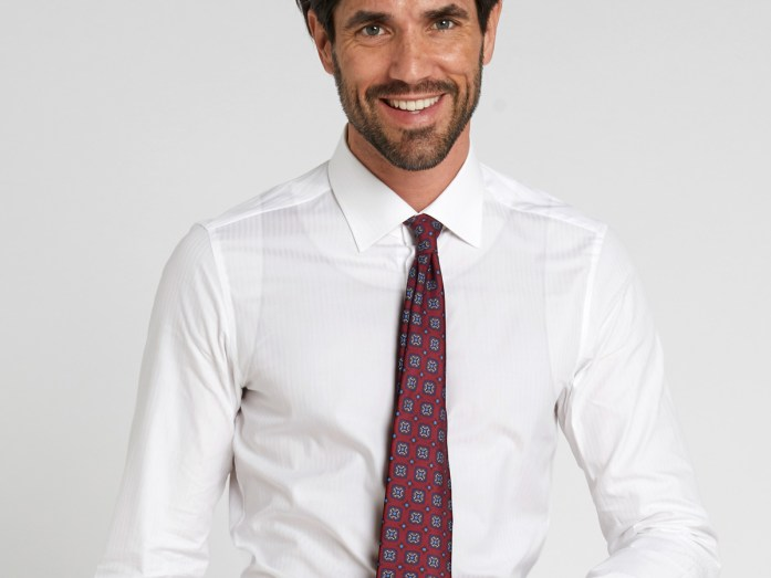 A man wears a white shirt with a transparent tank top and burgundy patterned tie