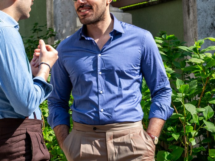 Detail on a man wearing an unstretched blue shirt and beige trousers
