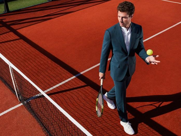 Un uomo vestito in abito elegante gioca su un campo da tennis