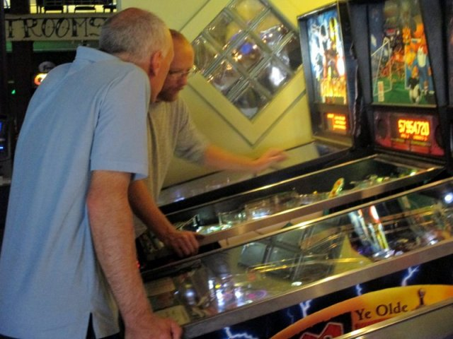 Derrick the pinball repairman consults with Chris.