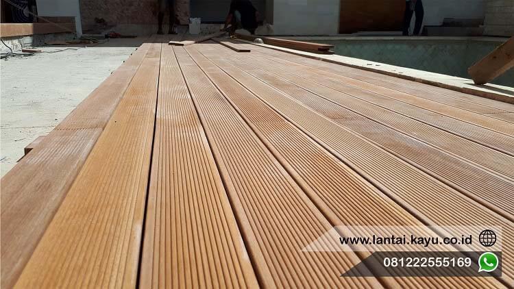 Pemasangan Decking kayu Ulin di area outdoor samping kolam renang