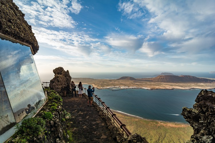 Tourists visiting Mirador del Rio. Lanzarote. Canary Islands. Spain. Lanzarote viewpoint during sunset and La Graciosa island in the background.