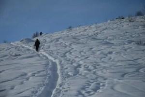 ciaspolatore sulla neve salendo a punta Sourela