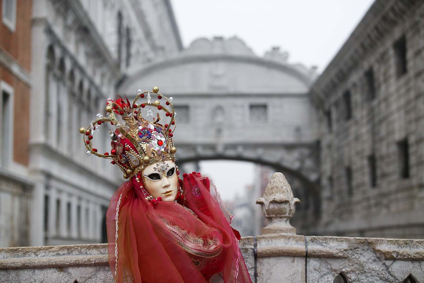 A masked reveller poses in front of the Ponte dei Sospiri (Bridge of Sighs) during the Venice Carnival January 30, 2016. REUTERS/Alessandro Bianchi