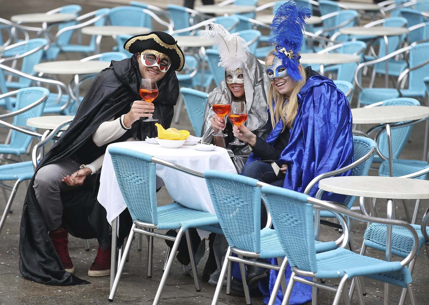 Masked revellers pose with their drinks in San Marco Piazza during the Venice Carnival, January 30, 2016. REUTERS/Alessandro Bianchi