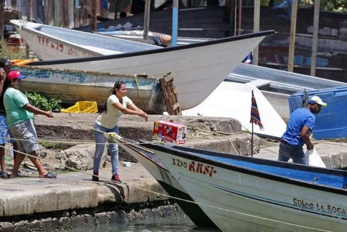 Venezolanos cargan en un bote mercancías, que son escasas en su país, mientras se preparan para volver a casa desde el puerto de San Fernando, al sur de Trinidad. Foto tomada el 15 de junio del 2016. REUTERS/Andrea De Silva
