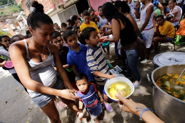 Children queue as they wait to receive free food which was prepared by residents and volunteers on a street in the low-income neighborhood of Caucaguita in Caracas, Venezuela September 17, 2016. REUTERS/Henry Romero