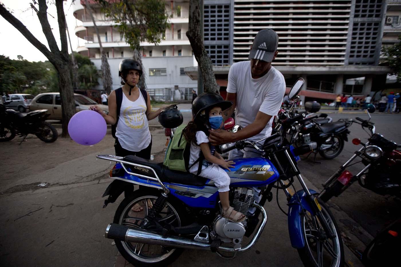 En esta imagen, tomada el 19 de septiembre de 2016, Maykol Pacheco, coloca un casco a su hija Ashley mientras se preparan para salir del hospital universitario de Caracas, Venezuela. Dos semanas después de sufrir un raspón en la rodilla, la niña se retorcía de dolor en la cama de un hospital. Le costaba respirar e imploraba a sus padres que le llevasen agua. (AP Foto/Fernando Llano)