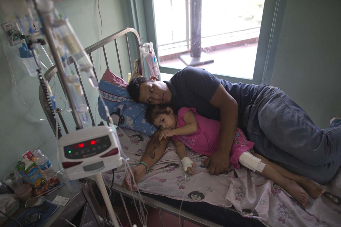 En esta imagen del 11 de agosto de 2016, Maykol Pacheco se acurruca con su hija Ashley en su cama de hospital, durante su estancia de dos meses en el Hospital Universitario de Caracas, en Venezuela. (AP Foto/Ariana Cubillos)
