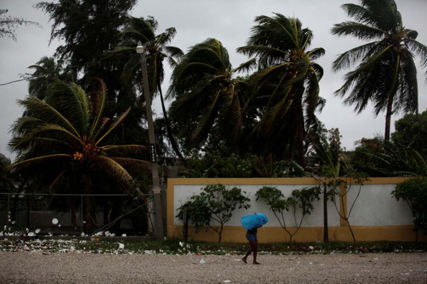 Una mujer se cubre de la lluvia provocada por la llegada del Huracán Matthew, en Les Cayes, Haití. 3 de octubre de 2016. Los haitianos que viven en chozas vulnerables frente al mar buscaban refugio en momentos en que el huracán Matthew, la tormenta caribeña más fuerte en nueve años, se acercaba al país y causaba mareas de tormenta, viento y lluvia en la costa. REUTERS/Andres Martinez Casares