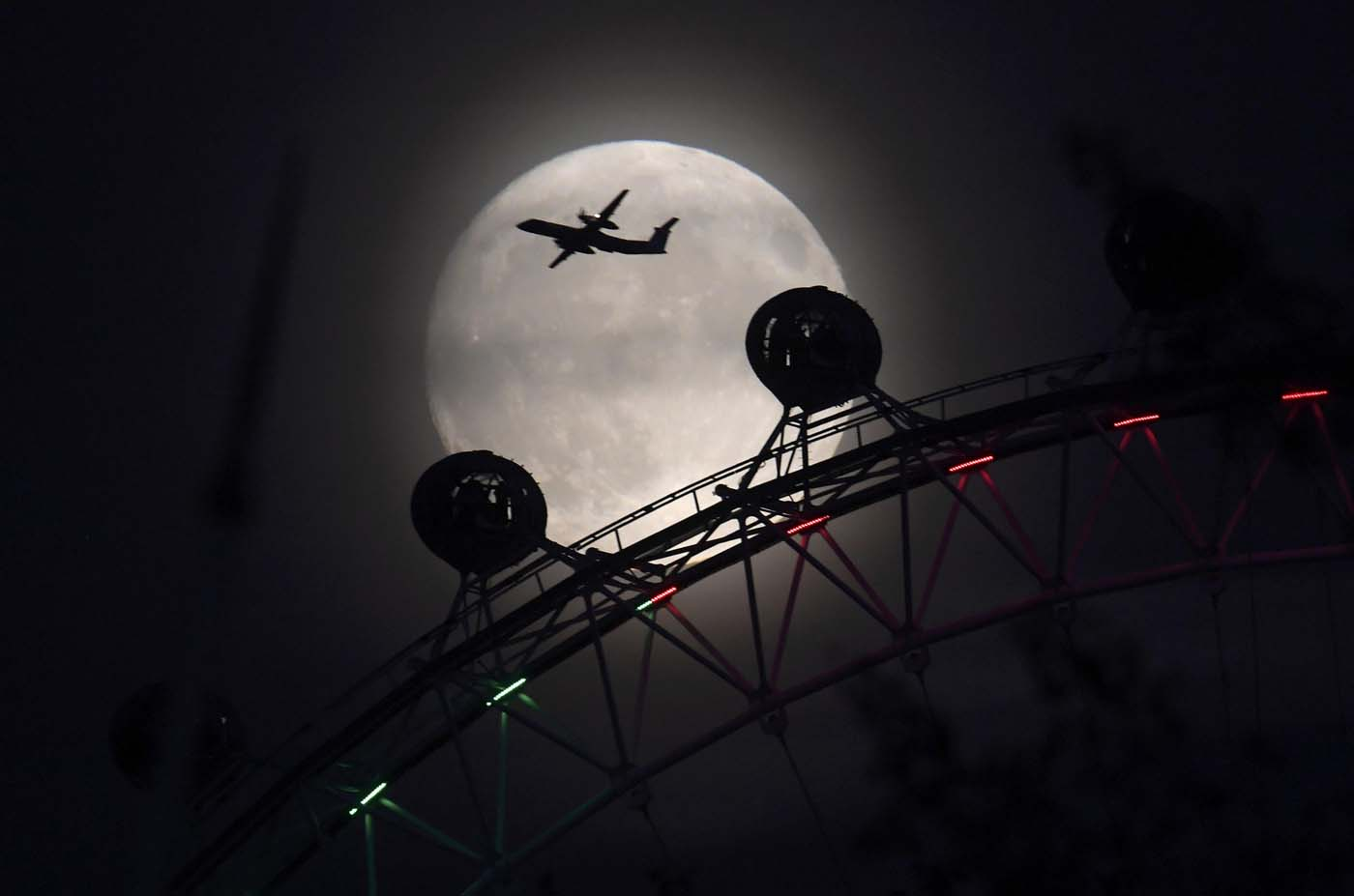 "An aeroplane flies past the London Eye wheel, and moon, a day before the ""supermoon"" spectacle in London, Britain, November 13, 2016. REUTERS/Toby Melville"