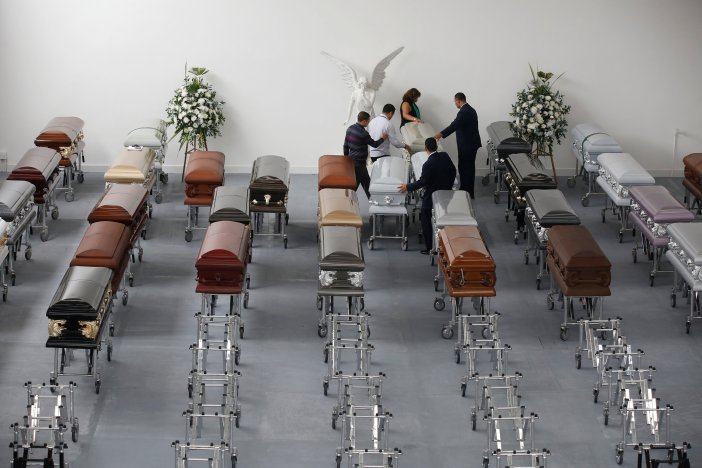 Funeral workers arrange coffins holding the remains of the victims who died in an accident of the plane that crashed into the Colombian jungle with Brazilian soccer team Chapecoense onboard, in Medellin, Colombia December 1, 2016. REUTERS/Jaime Saldarriaga