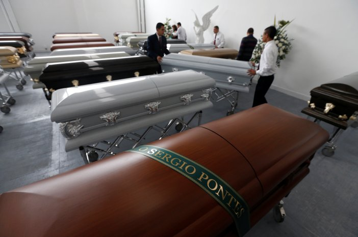 Funeral workers arrange coffins near the coffin holding the remains of former soccer player and sports commentator Mario Sergio Pontes who died along with others in an accident of the plane that crashed into the Colombian jungle with Brazilian soccer team Chapecoense onboard, in Medellin, Colombia December 1, 2016. REUTERS/Jaime Saldarriaga