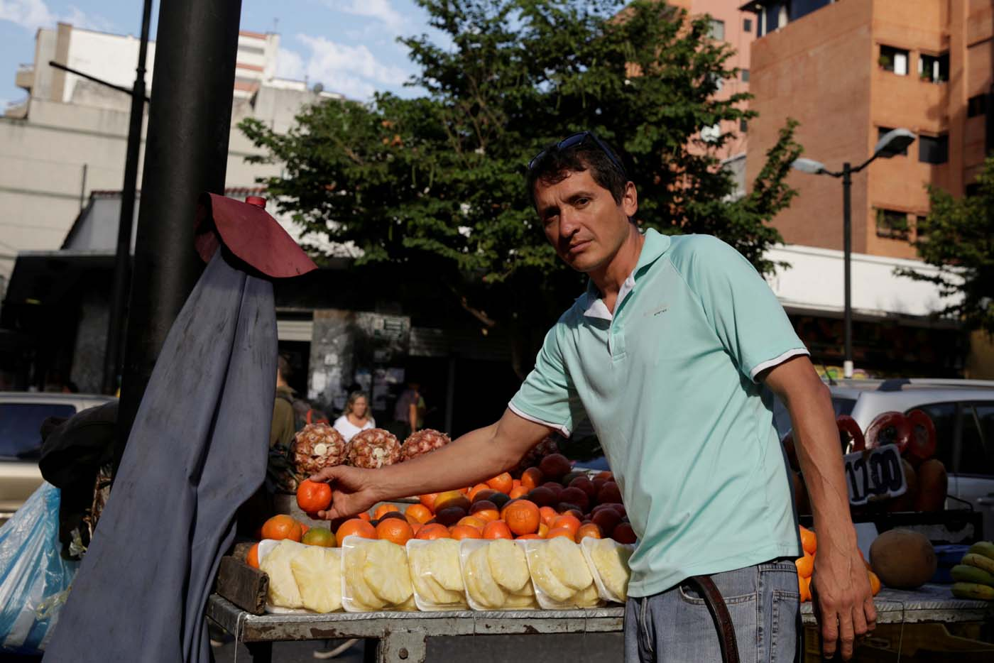 Jesus Pena sells fruits at his stall in a street of Chacao, in Caracas, Venezuela February 24, 2017. Picture taken February 24, 2017. REUTERS/Marco Bello