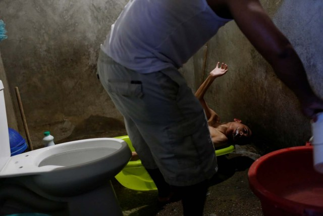 """Miguel Anton (C) baths his son Jose Gregorio Anton, 11, a neurological patient being treated with anticonvulsants, at their house in La Guaira, Venezuela February 15, 2017. REUTERS/Carlos Garcia Rawlins SEARCH """"EPILEPSY CARACAS"""" FOR THIS STORY. SEARCH """"WIDER IMAGE"""" FOR ALL STORIES."""
