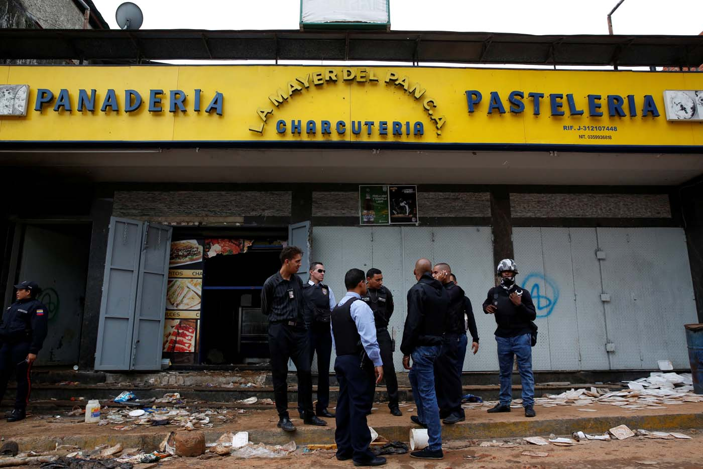 REFILE - UPDATING SLUG Police officers and criminal investigators stand in front of a bakery, after it was looted in Caracas, Venezuela April 21, 2017. REUTERS/Carlos Garcia Rawlins