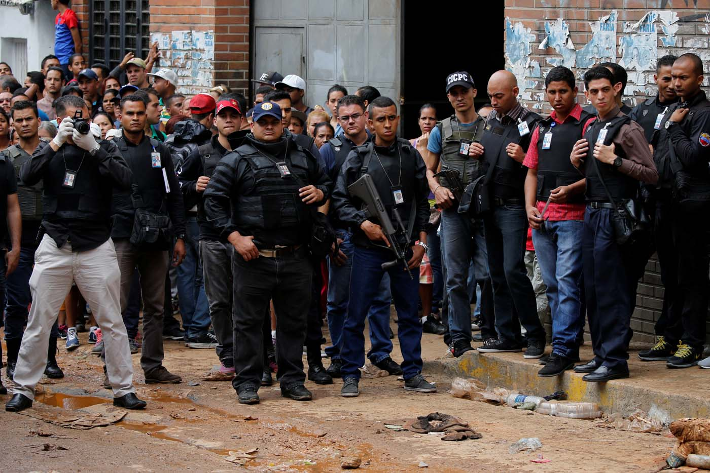 Police officers and criminal investigators look for evidence in front of a bakery, after it was looted in Caracas, Venezuela April 21, 2017. REUTERS/Carlos Garcia Rawlins