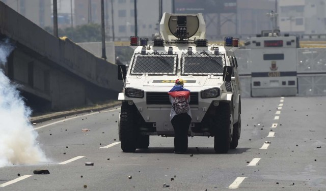 """(FILES) This file photo taken on April 19, 2017 shows a demonstrator standing in front of an armoured vehicle of the riot police during a rally against Venezuelan President Nicolas Maduro, in Caracas on April 19, 2017. """"It hurt me to see how they were firing at the kids,"""" she said later, referring to the rubber bullets and tear gas used by police against protesters.  / AFP PHOTO / Juan BARRETO"""