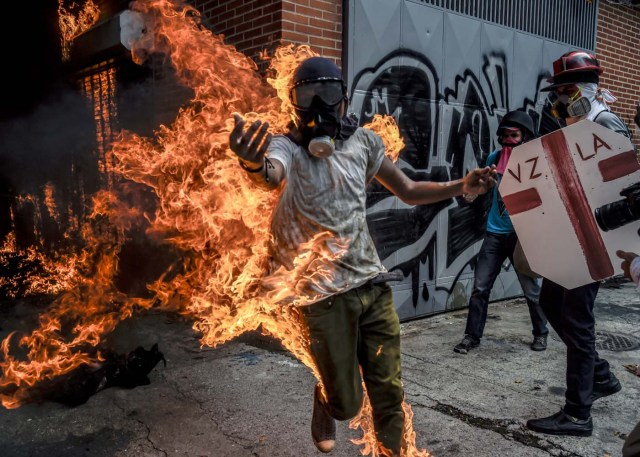 """(FILES) This file photo taken on May 03, 2017 shows a demonstrator catching fire after the gas tank of a police motorbike exploded during clashes in a protest against Venezuelan President Nicolas Maduro, in Caracas on May 3, 2017. From his hospital bed where he lay in bandages with burns on 70 percent of his body, Victor Salazar sent a video urging protesters: """"Get out into the street, not for me but for Venezuela."""" / AFP PHOTO / JUAN BARRETO"""