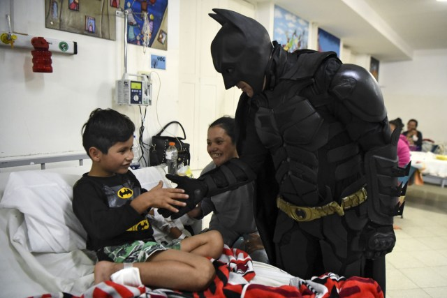 Pablo Valdez (L), 7, who is hospitalized with an infection that prevents him fom walking, is cheered up by Argentine Batman at the 'Sor Maria Ludovica' children's Hospital in La Plata, 60 kilometres south of Buenos Aires, on June 2, 2017.  The Argentine Batman has made La Plata children's hospital a target of laughter and treats against pain. / AFP PHOTO / Eitan ABRAMOVICH / TO GO WITH AFP STORY BY PAULA BUSTAMANTE MORE PICTURES IN AFPFORUM