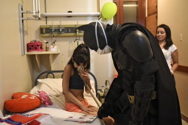 This picture taken through a window, shows Florencia Aguero (L), a cystic fibrosis patient, playing with Argentine Batman at the 'Sor Maria Ludovica' children's Hospital in La Plata, 60 kilometres south of Buenos Aires, on June 2, 2017.  The Argentine Batman has made La Plata children's hospital a target of laughter and treats against pain. / AFP PHOTO / Eitan ABRAMOVICH / TO GO WITH AFP STORY BY PAULA BUSTAMANTE MORE PICTURES IN AFPFORUM