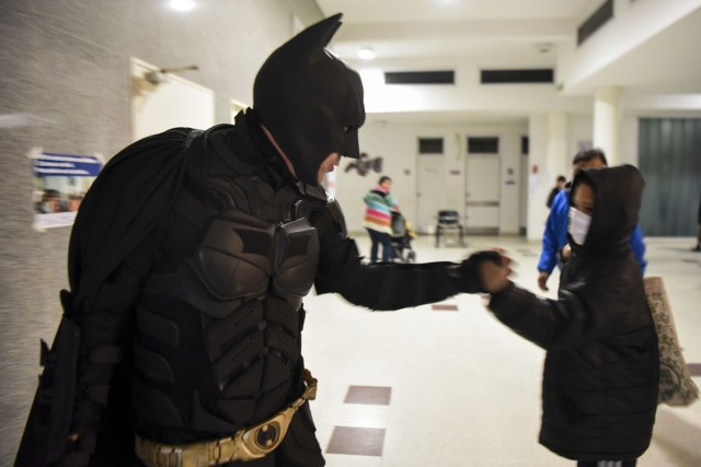 Argentine Batman greets a boy as he leaves the 'Sor Maria Ludovica' children's Hospital in La Plata, 60 kilometres south of Buenos Aires, on June 2, 2017.  The Argentine Batman has made La Plata children's hospital a target of laughter and treats against pain. / AFP PHOTO / Eitan ABRAMOVICH / TO GO WITH AFP STORY BY PAULA BUSTAMANTE MORE PICTURES IN AFPFORUM