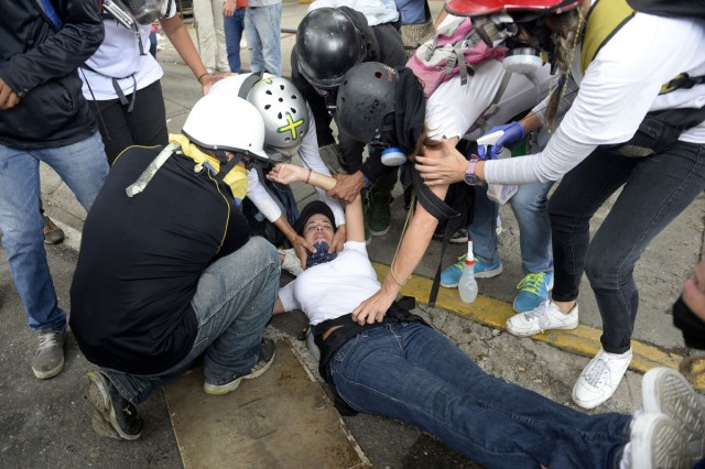 "Opposition demonstrators assist an injured fellow activist during the ""Towards Victory"" protest against the government of President Nicolas Maduro in Caracas on June 10, 2017.  Clashes at near daily protests by demonstrators calling for Maduro to quit have left 66 people dead since April 1, prosecutors say.  / AFP PHOTO / FEDERICO PARRA"