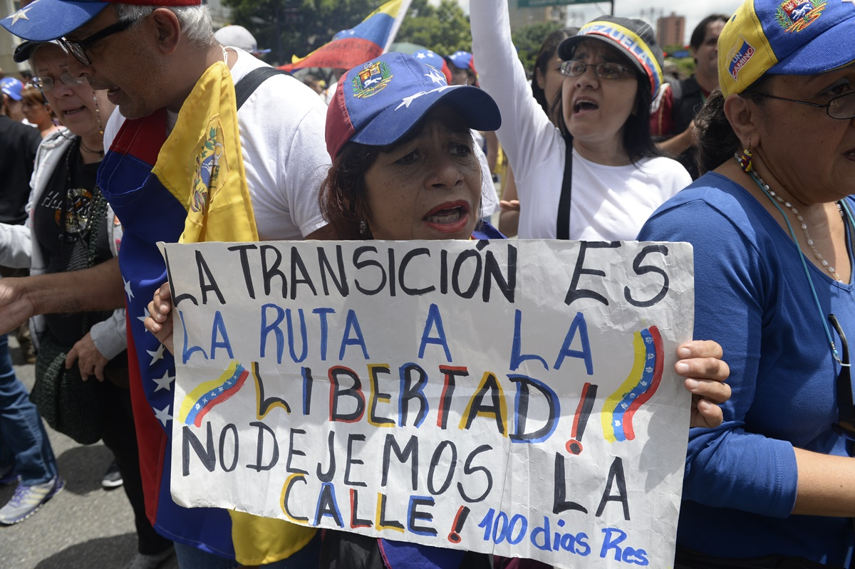Opposition activists demonstrate against Venezuelan President Nicolas Maduro in Caracas, on July 9, 2017. Venezuela hit its 100th day of anti-government protests on Sunday, one day after its most prominent political prisoner, Leopoldo Lopez, vowed to continue his fight for freedom after being released from jail and placed under house arrest. At least 91 people have died since non-stop street protests began on April 1. / AFP PHOTO / Federico PARRA