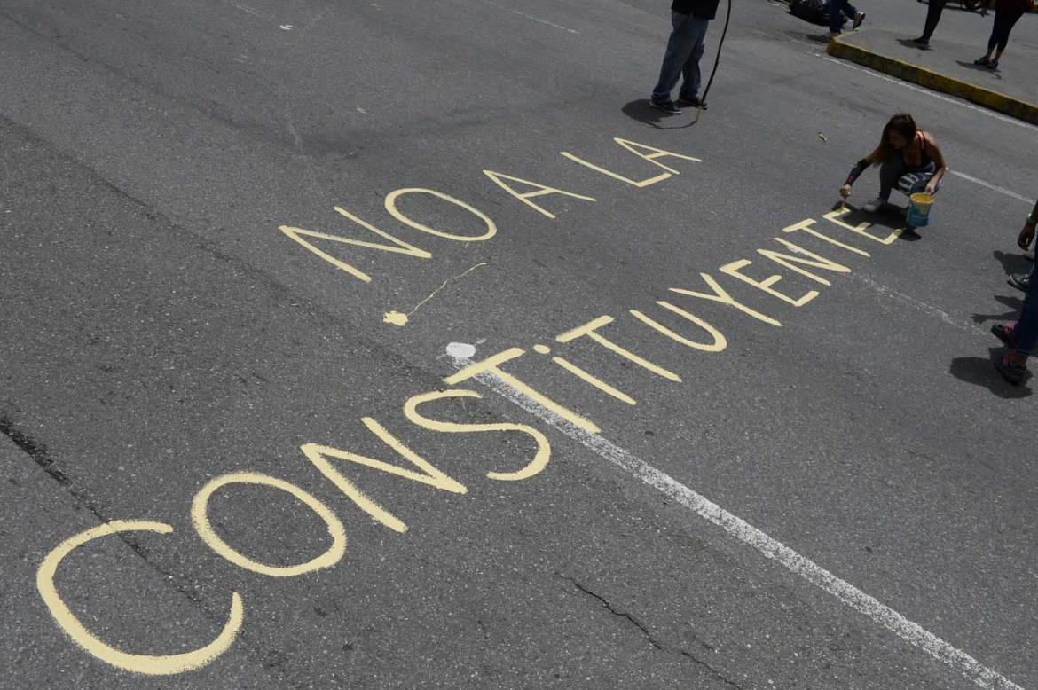 "Venezuelan opposition activists write ""No to the Constituent (Assembly)"" during an anti-government protest in Caracas on July 10, 2017. Venezuela hit its 100th day of anti-government protests Sunday, amid uncertainty over whether the release from prison a day earlier of prominent political prisoner Leopoldo Lopez might open the way to negotiations to defuse the profound crisis gripping the country. / AFP PHOTO / FEDERICO PARRA"