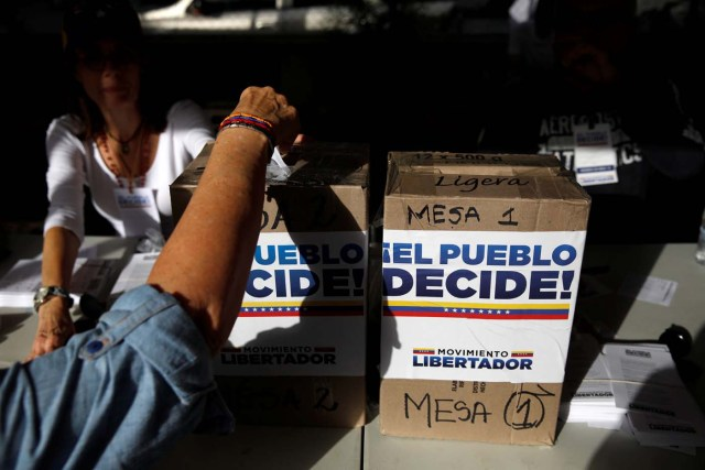 A person votes during an unofficial plebiscite against Venezuela's President Nicolas Maduro's government and his plan to rewrite the constitution, in Caracas, Venezuela July 16, 2017. The writing on the boxes read