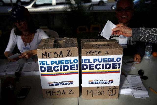 A woman casts her vote during an unofficial plebiscite against Venezuela's President Nicolas Maduro's government and his plan to rewrite the constitution, in Caracas, Venezuela July 16, 2017. The writing on the boxes read