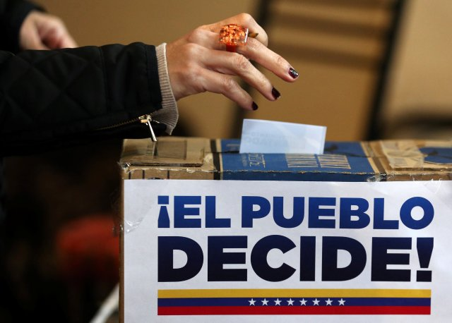 A Venezuelan woman living in Argentina casts her vote during an unofficial plebiscite against President Nicolas Maduro's government in Buenos Aires, Argentina, July 16, 2017. The sign reads