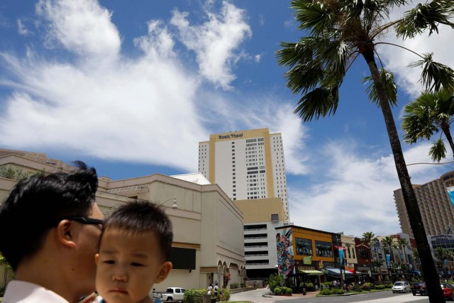 A South Korean tourist carries his child in the Tumon tourist district on the island of Guam, a U.S. Pacific Territory, August 10, 2017. REUTERS/Erik De Castro
