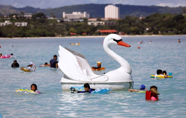 A floater in the shape of a swan is pictured along with tourists on the island of Guam, a U.S. Pacific Territory, August 12, 2017. REUTERS/Erik De Castro