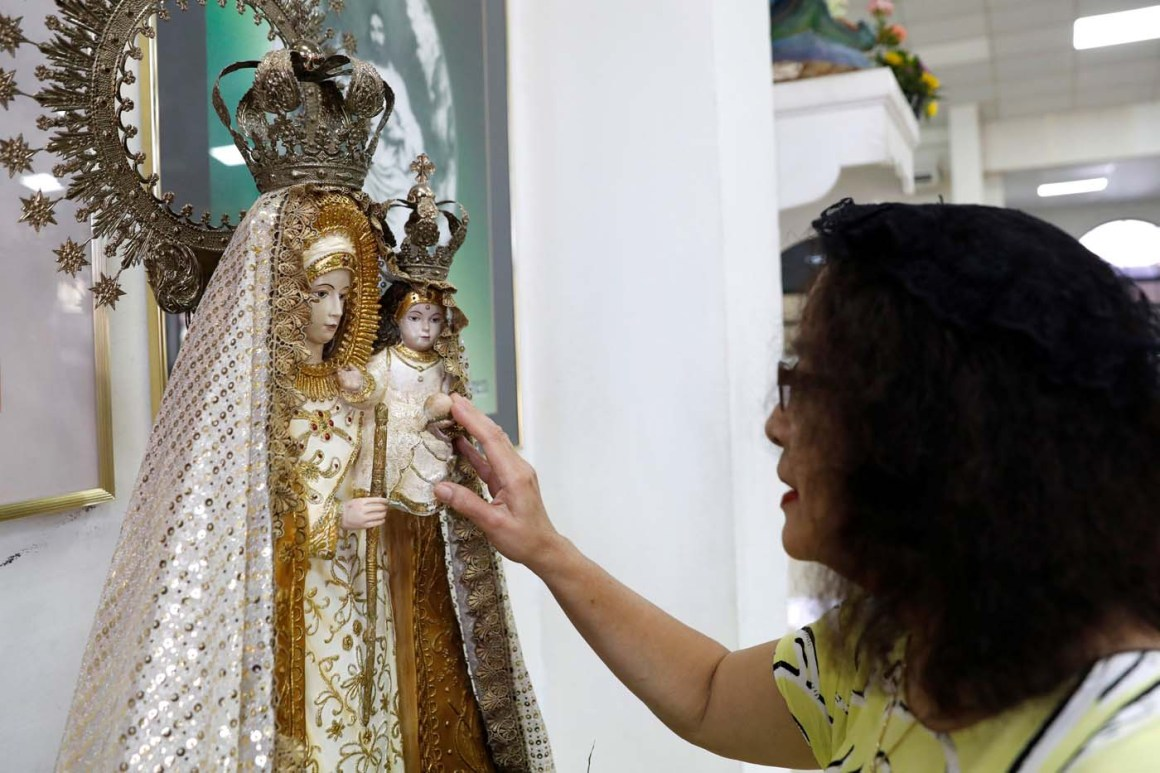 A woman pays homage to an image of Virgin Mary and baby Jesys after attending a Sunday mass at Sta Barbara Church on the island of Guam, a U.S. Pacific Territory, August 13, 2017.  REUTERS/Erik De Castro