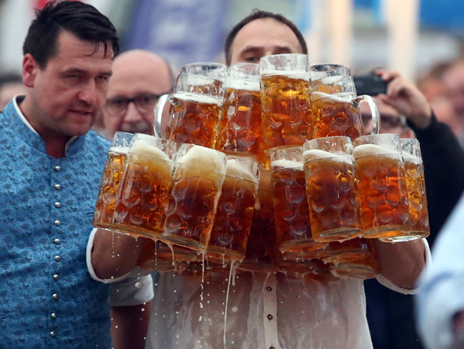 German Oliver Struempfel competes to set a new world record in carrying one liter beer mugs over a distance of 40 m (131 ft 3 in) in Abensberg, Germany September 3, 2017. Struempfel carried 29 mugs over 40 meters to set a new world record. REUTERS/Michael Dalder