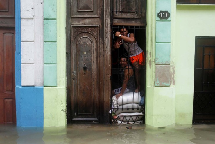 People pose for a photograph as sandbags are placed in the entrance of a home, after the passing of Hurricane Irma, in Havana, Cuba September 10, 2017.  REUTERS/Stringer NO SALES. NO ARCHIVES
