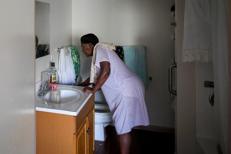 Marie Delva, de 64 años, intenta vaciar su excusado en el centro de asistencia Cypress Run en Immokalee, EEUU / Reuters