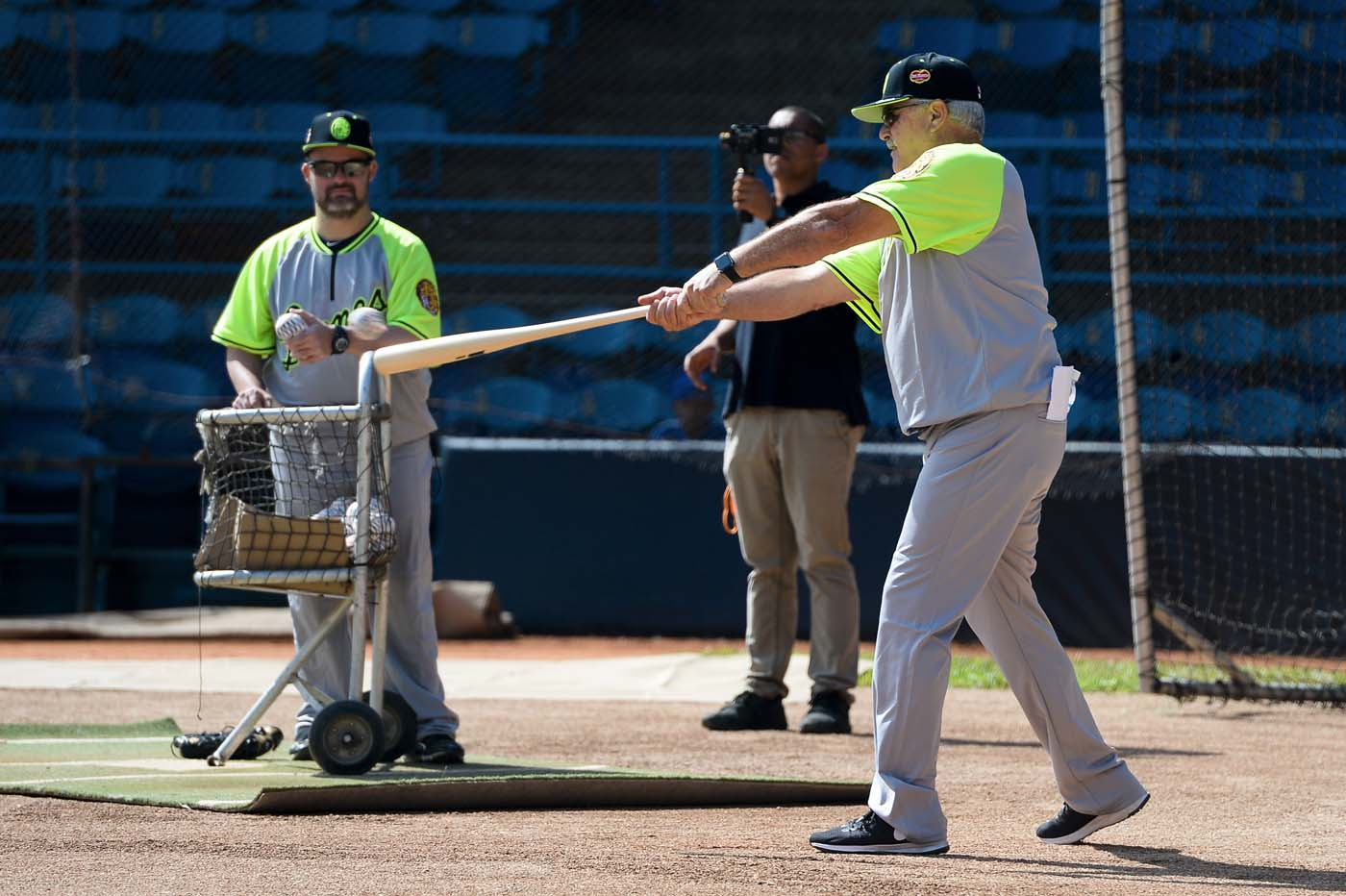 Mike Rojas (R), manager of the Venezuelan baseball team Leones del Caracas, attends a training session at the Universitario stadium in Caracas, on September 18, 2017. While baseball is Venezuela's national sport, some fans are angry that the government, given the severity of the economic crisis and the political tension, will spend nearly ten million dollars on organizing the upcoming Winter League rather than on imports of food and medicine. / AFP PHOTO / FEDERICO PARRA