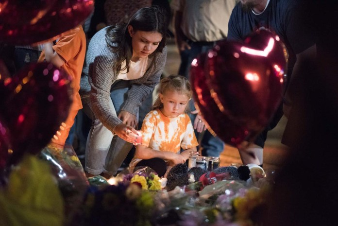 A woman places a candle as a young girl looks on at a makeshift memorial near the Mandalay Hotel on the Las Vegas Strip, in Las Vegas, Nevada on October 3, 2017, after a gunman killed 58 people and wounded more than 500 others, before taking his own life, when he opened fire from a hotel on a country music festival. Police said the gunman, a 64-year-old local resident named as Stephen Paddock, had been killed after a SWAT team responded to reports of multiple gunfire from the 32nd floor of the Mandalay Bay, a hotel-casino next to the concert venue. / AFP PHOTO / Robyn Beck