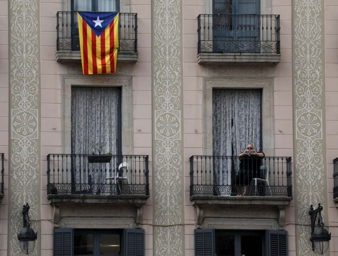 A woman takes a picture as people attend a protest called by pro-independence groups for citizens to gather at noon in front of city halls throughout Catalonia, in Plaza Sant Jaume in Barcelona, Spain October 2, 2017. REUTERS/Susana Vera