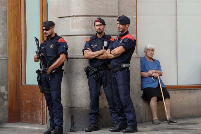 Catalan regional police officers stand guard in Plaza Sant Jaume during a protest called by pro-independence groups for citizens to gather at noon in front of city halls throughout Catalonia, in Barcelona, Spain October 2, 2017. REUTERS/Yves Herman