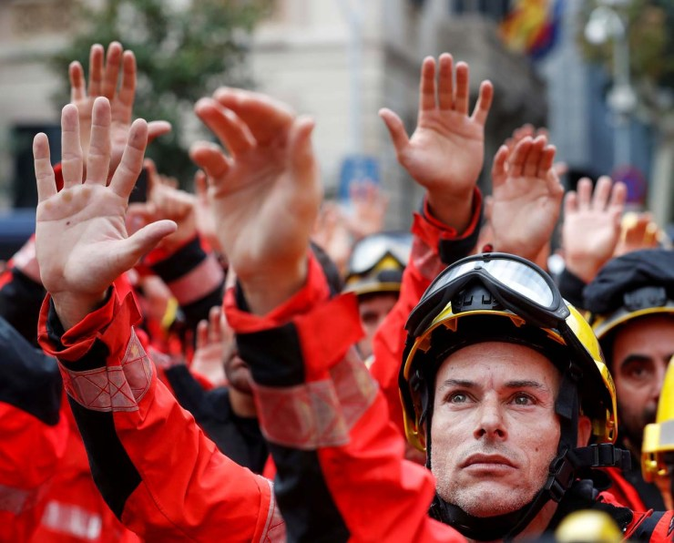 Firefighters hold up their hands during a demonstration called to protest against police actions during the banned independence referendum in Barcelona, Spain October 3, 2017. REUTERS/Yves Herman