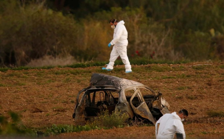 Forensic experts walk in a field after a powerful bomb blew up a car (Foreground) and killed investigative journalist Daphne Caruana Galizia in Bidnija, Malta, October 16, 2017. REUTERS/Darrin Zammit Lupi TPX IMAGES OF THE DAY