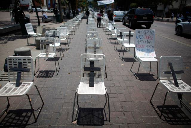 Anti-government protesters placed black crosses on white chairs, representing victims who died from violence, during a demonstration in Caracas