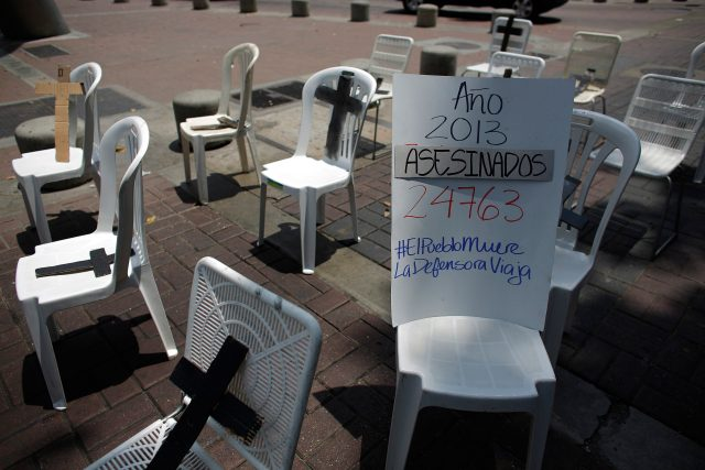Placard showing the number of victims of violence during 2013, is seen along black crosses during an anti-government protest in Caracas
